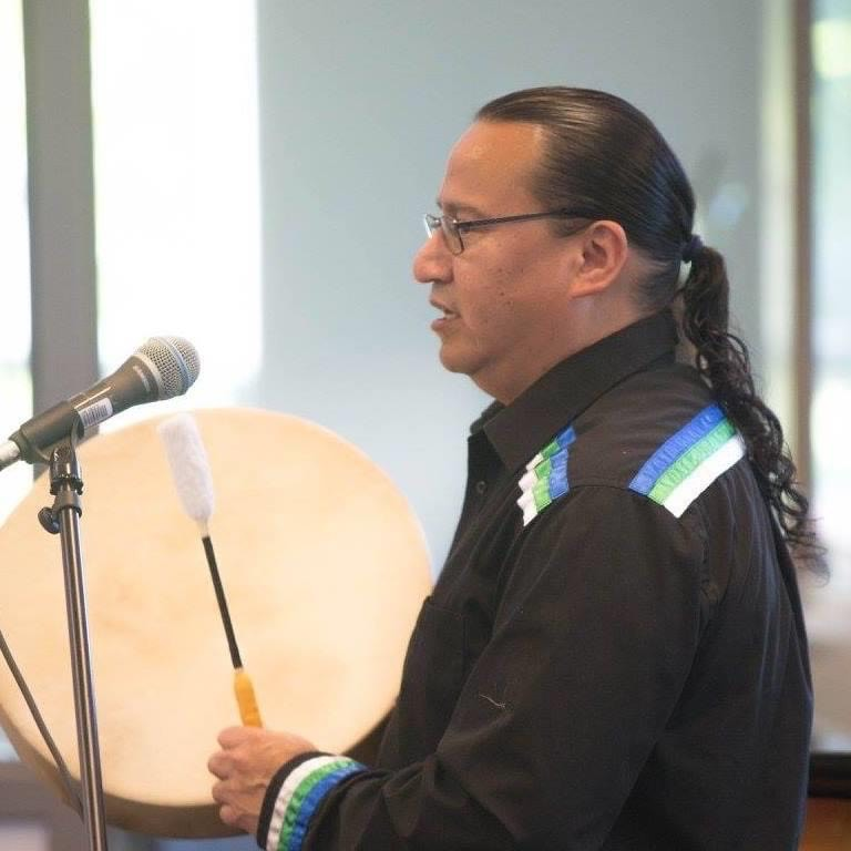 Indigenous man's side profile, playing a hand drum at a microphone.