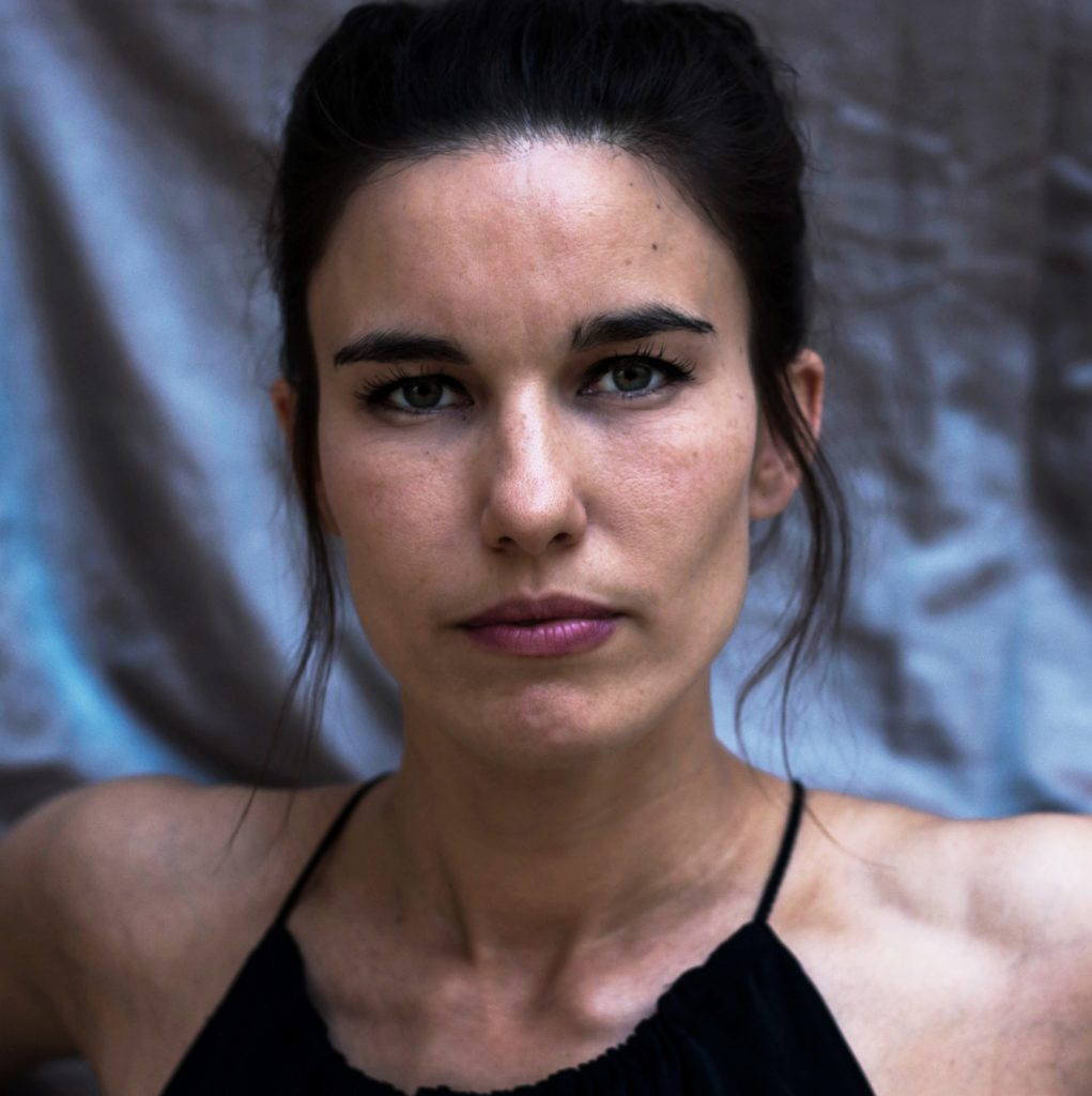 Headshot of a woman with dark hair and dark eyes. Her hair is pulled back out of her face. She looks calm.