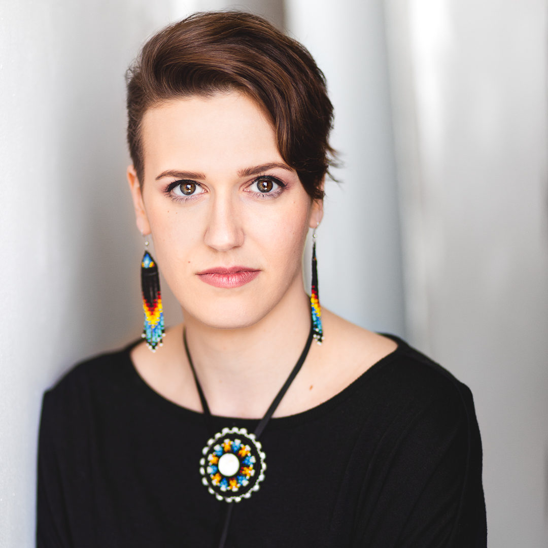 Headshot of a woman with short hair, wearing beaded earrings and matching necklace. She is wearing black and standing in front of a white backdrop.